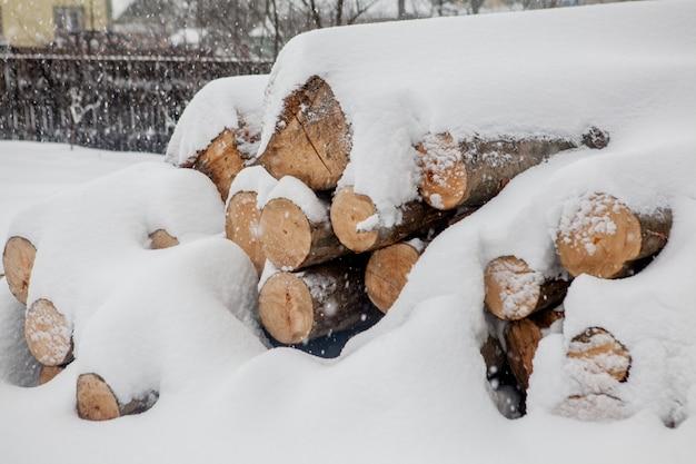 雪の下で倒れた木。木工産業の原料。戸外での木材の保管。木材会社。木材。ラウンドウッド。丸太