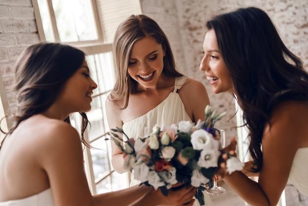 結婚式に興奮した。彼女の魅力的な花嫁介添人と話している間、結婚式の花束を持って微笑んでいる魅力的な若い花嫁