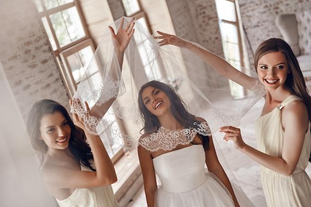 とても幸せに落ちました!花嫁介添人がベールをかぶるのを手伝って、試着室に立っている間笑顔