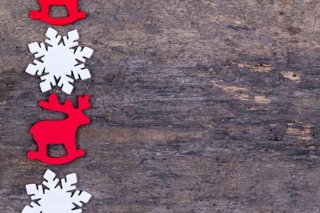 Felt christmas toys or decorations laid in a line on a wooden background. christmas deer, snowflake