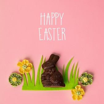 Felt easter decorations and sweets on pink background