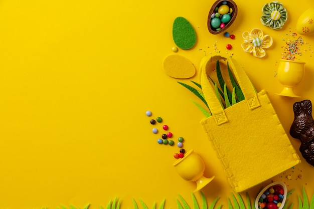 Felt easter decorations and sweets on yellow background