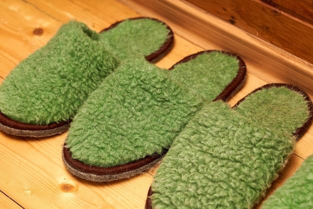Войлочные зеленые тапочки для гостей на деревянном полу в коридоре