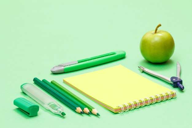 緑の背景にフェルトペン、色鉛筆、ノート、ペーパーナイフ、コンパス、リンゴ。学校のコンセプトに戻ります。学用品。浅い被写界深度。