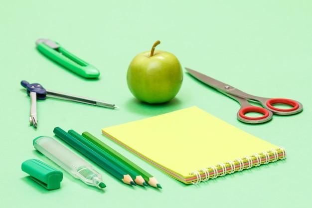 緑の背景にフェルトペン、色鉛筆、ノートブック、リンゴ、コンパス、ペーパーナイフ、はさみ。学校のコンセプトに戻ります。学用品。浅い被写界深度。