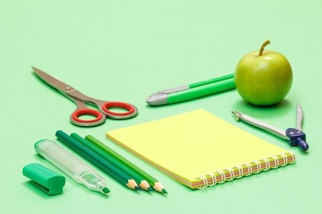 Фломастер, цветные карандаши, блокнот, ножницы, нож для бумаги, компас и яблоко на зеленом фоне. снова в школу концепции. школьные принадлежности. малая глубина резкости.