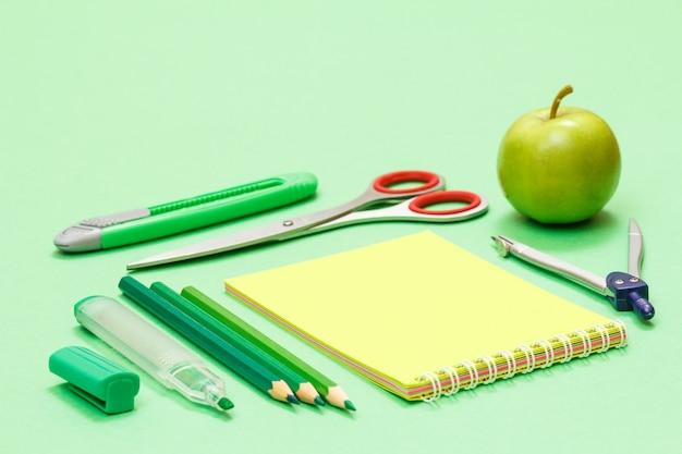 Фломастер, карандаши, блокнот, ножницы, нож для бумаги, компас и яблоко на зеленом фоне. снова в школу концепции. школьные принадлежности. малая глубина резкости.