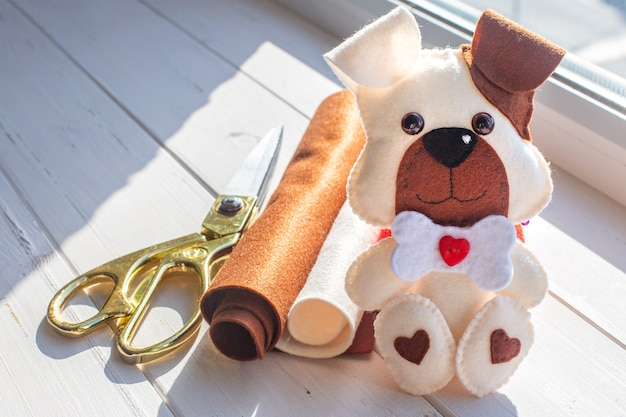 Felt puppy and sewing supplies on wooden table