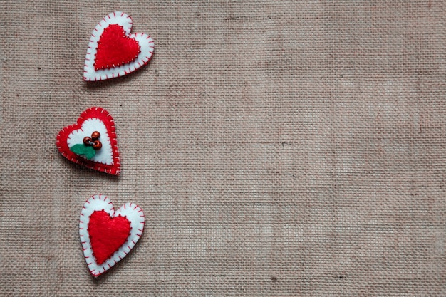 Felt red and white hears on the hessian background. st valentines day concept.