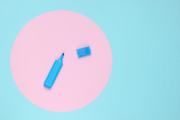Felt-tip pen on blue background with pink pastel circle. top view.