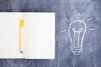 Felt tip pen on blank notebook with drawn light bulb on chalkboard