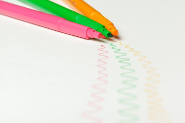 Felt-tip pens with drawn color marks on white background