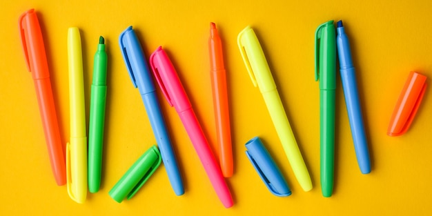 Felt-tip pens on a yellow background with copy space