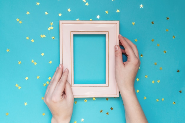 Femal hand holding pink foto frame on blue wall with scattered gold stars. creative mockup.