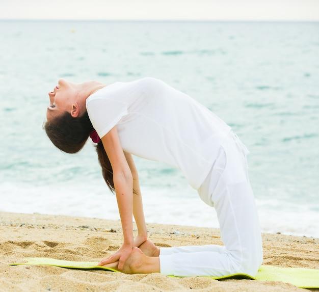 20-30 세의 여성은 바다 근처 해변에서 흰 티셔츠로 스트레칭 연습을하고 있습니다.