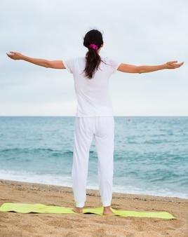 Женщине 20-30 лет остается и практикует медитацию в белой футболке на пляже.