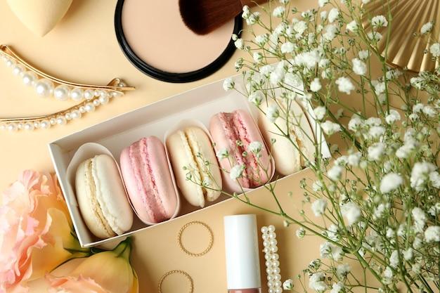 Женские аксессуары и миндальное печенье на бежевом фоне