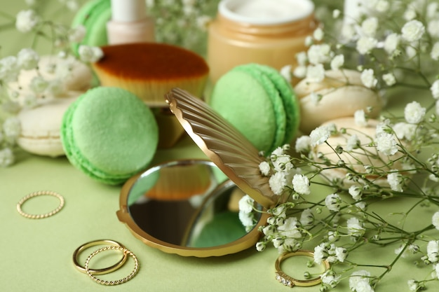 녹색 배경에 여성 액세서리와 마카롱