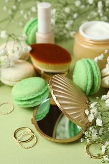 Женские аксессуары и миндальное печенье на зеленом фоне