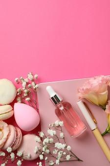 Женские аксессуары и миндальное печенье на розовом фоне
