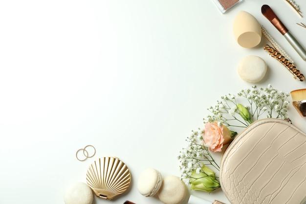 Женские аксессуары и миндальное печенье на белом фоне