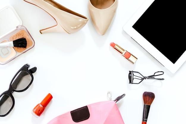 Женские аксессуары и обувь с косметическим набором на белом фоне