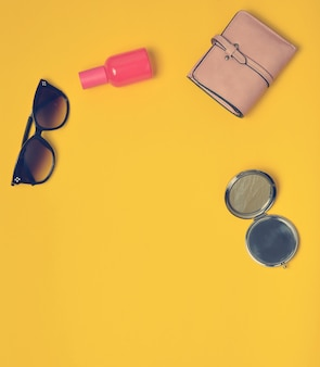 Female accessories isolated on a yellow surface