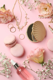 Female accessories and macaroons on pink background