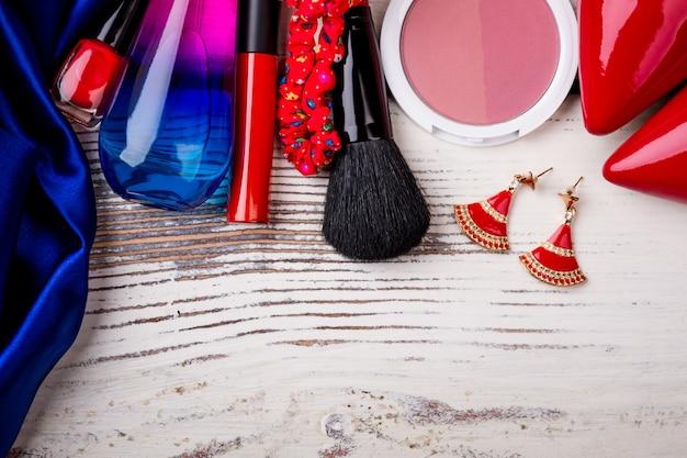 나무 배경 루즈 귀걸이와 매니큐어에 여성 액세서리는 당신의 아름다움을 표현합니다