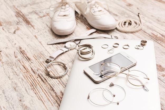 白い木製のテーブルの上のラップトップと携帯電話を持つ女性のアクセサリー