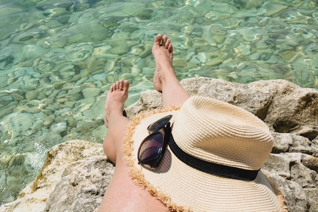 Female accessory, straw sunhat, glasses and long legs. clean sea. summer vacation. close up.