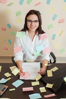 Female accountant in glasses sitting at workplace