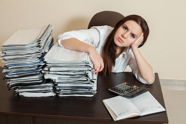 Female accountant hugs big stacks of documents