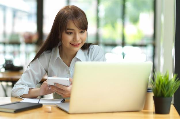 カフェのコワーキングスペースでノートパソコンと電卓を扱う女性会計士
