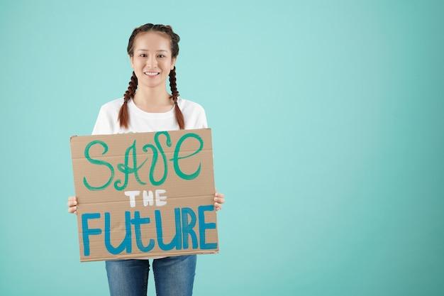 Активистка, держащая спасите будущее бумажный знак, изолированный на голубом