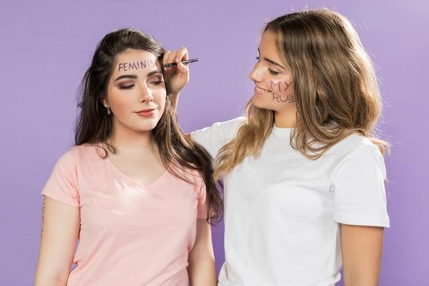 Attiviste femminili che dipingono i loro volti