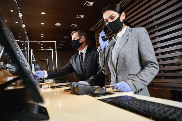 男性の受付係が訪問者を助けている間、女性の管理者が電話に応答します。それらの医療用マスクとゴム手袋
