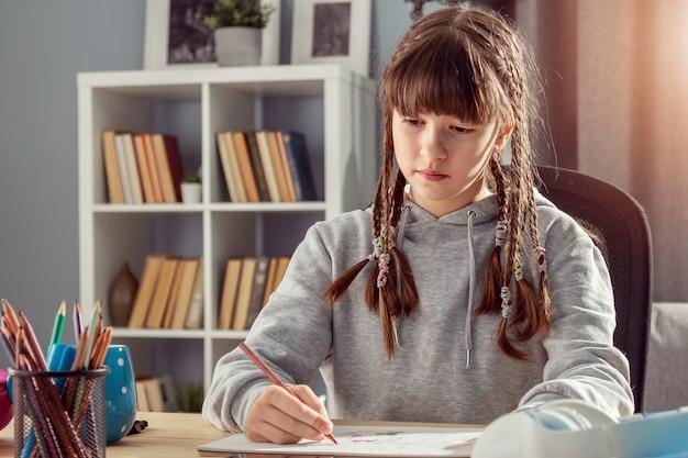 Девушка-подросток учится из дома пишет или рисует что-то, сидя за столом, вид спереди