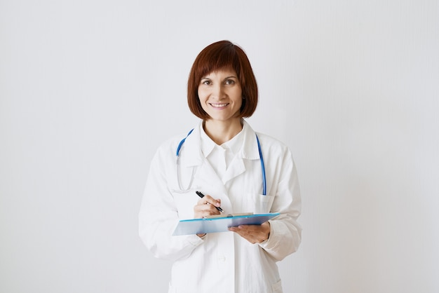 Female adult doctor stands on white background. beautiful woman, thinking, smiling, writing.