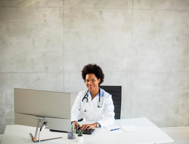 청진기는 사무실에서 책상 뒤에 앉아 흰색 코트를 입고 여성 아프리카 계 미국인 의사