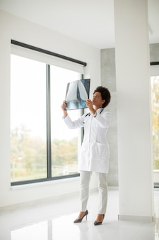 Афро-американский врач женщина в белом халате со стетоскопом стоит у окна в офисе и смотрит на рентгеновское изображение
