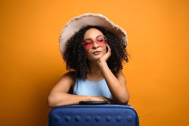 色の背景にスーツケースを持つ女性のアフリカ系アメリカ人旅行者
