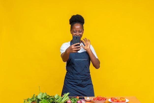 ビデオ通話をしているアフリカの女性シェフ、彼女の電話で手を振る