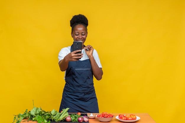 ビデオ通話をしながら笑っているアフリカの女性シェフ