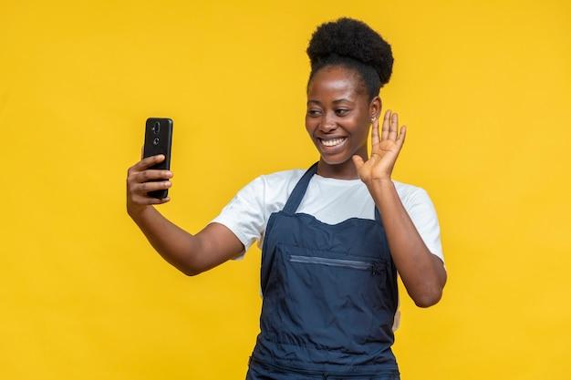 ビデオコールで誰かに手を振っているアフリカの女性シェフ