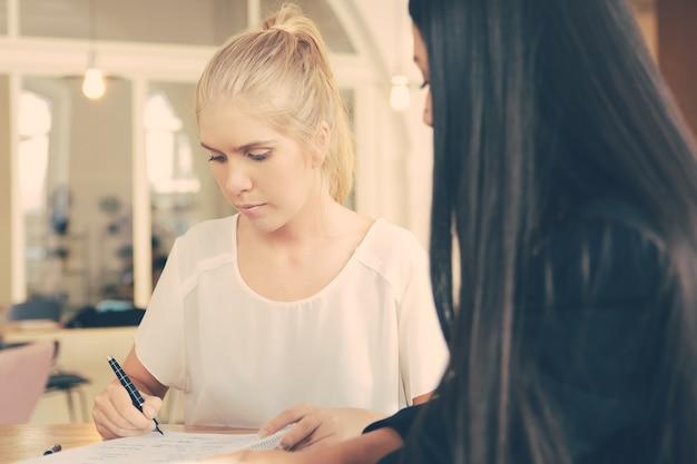 계약서에 서명하기 위해 코 워킹에서 여성 에이전트 및 고객 회의. 문서에 쓰는 여자