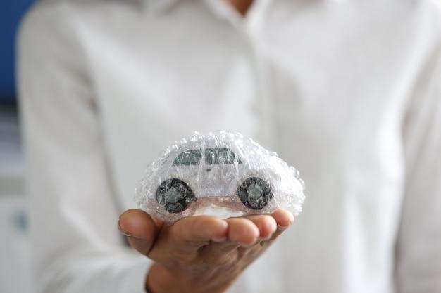 여성 에이전트가 거품 비닐 봉지 자동차 보험 개념으로 포장된 장난감 자동차를 들고 있다