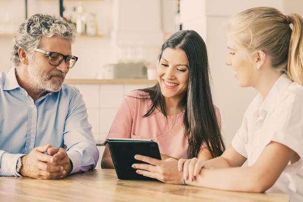 Incontro femminile agente o manager con coppia di clienti giovani e maturi, presentando il contenuto sul tablet