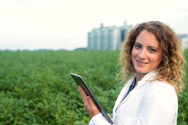 フィールドにタブレットを持つ女性農学者