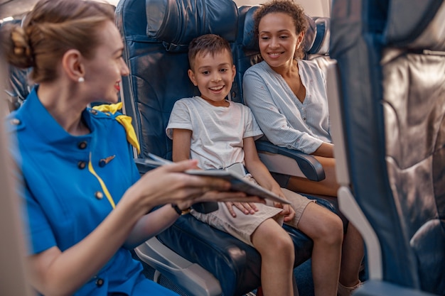 Female air hostess trying to entertain a kid on the plane by offering a book to read. cabin crew provide service to family in airplane. airline transportation and tourism concept